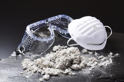 A pile of Asbestos sitting next to a pair of safety goggle and a breathing mask.