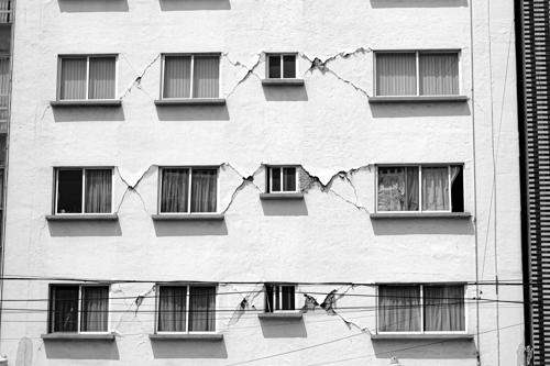 An apartment building with a faulty foundation resulting in cracks in the walls.