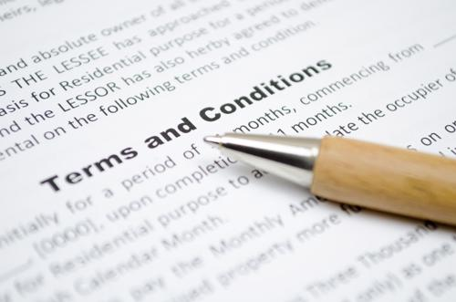 A closeup of the terms and conditions section of a contract with a pen sitting on top of them.