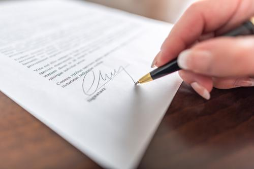 A close-up of a woman hand signing a contract.