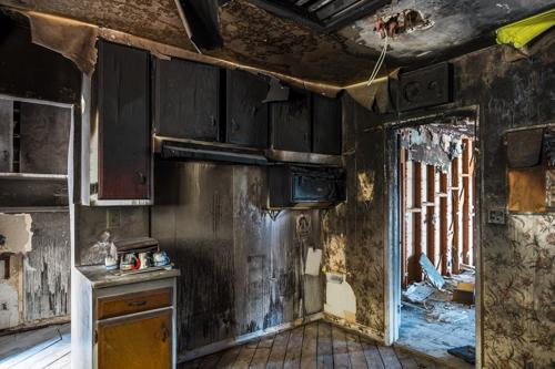 An interior shot of a kitchen with extensive fire damage.