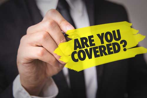 """A man holding a sticker that says """"are you covered?""""."""