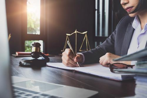 An attorney reviewing details of a contract litigation case at a desk.