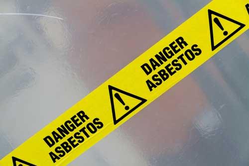 "Caution tape that reads ""danger asbestos""."