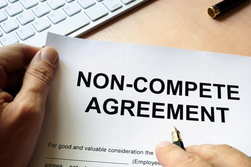 A man signing a non compete agreement.