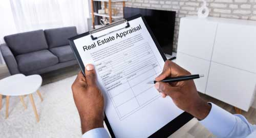 An individual who a clipboard with a real estate appraisal checklist.