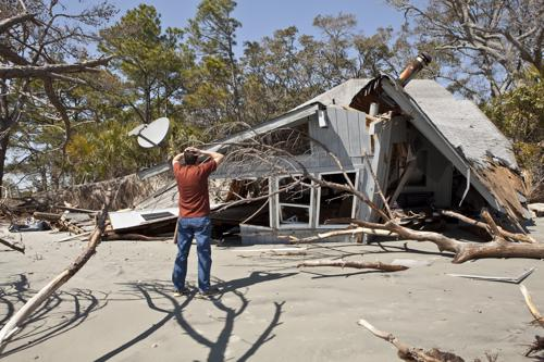 A distraught man looking at his house after a tree fell on it. Contact our New York property damage lawyers if this happens to you.