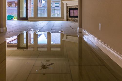 A living room floor flooded with water from a burst pipe. Our New York Water Damage Attorneys can negotiate insurance claims for situations like this.
