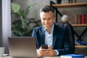 Hombre de negocios, en el escritorio, enviar mensajes de texto